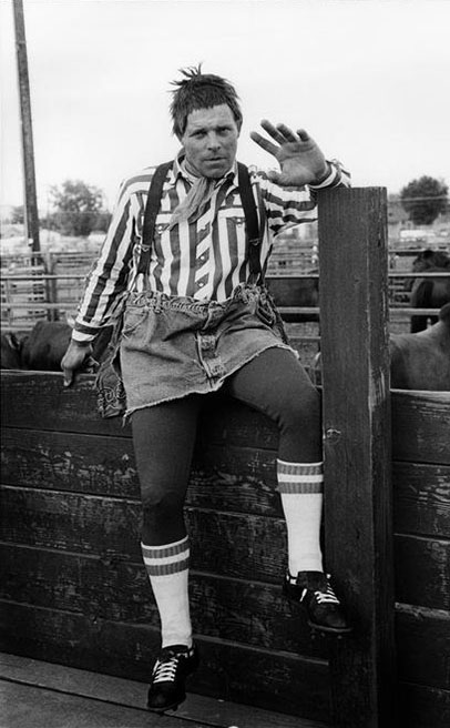 A rodeo clown sits on a fence with a hand raised towards the camera.