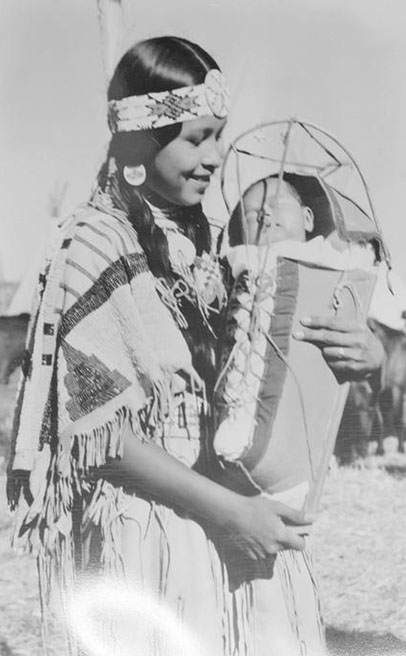 A smiling woman in Native American attire holds a sleeping baby that is secured in a cradleboard.