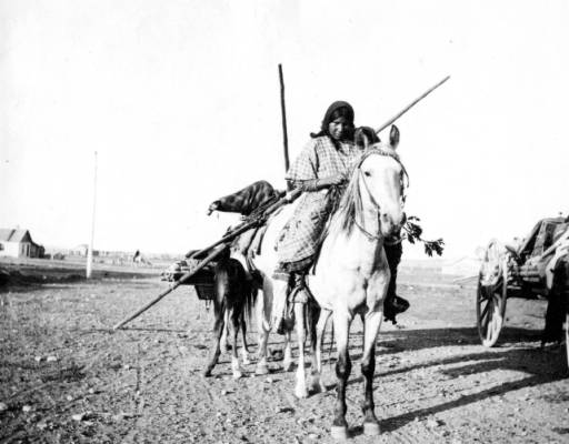 Native American girl on horse. Wagon on right