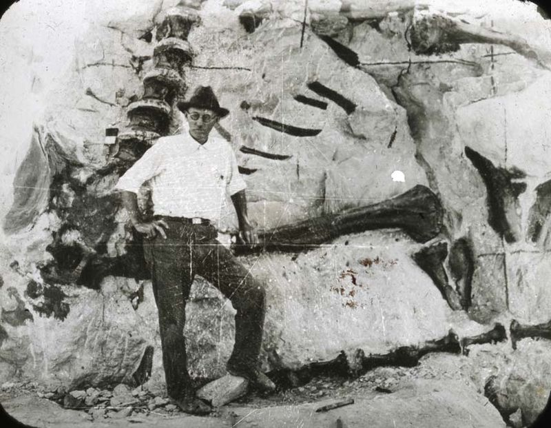 Earl Douglass striking a pose in front of what appear to be fossils embedded in rock.