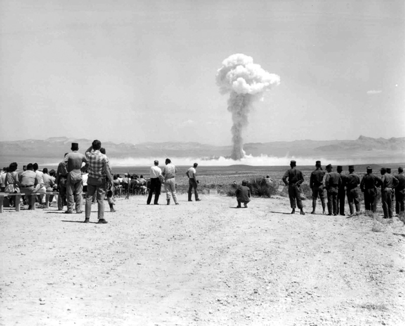 Onlookers viewing a nuclear explosion in the distance.