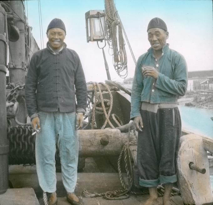 Hand tinted image of two Asian men stand on the deck of a junk boat posing for the camera.