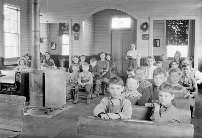 A group of young students seated in a classroom with their teacher in the Latham school, located in Lane County, Oregon.