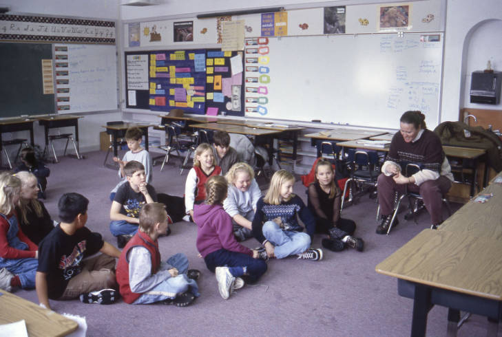 4th grade class sitting on the floor and listening to their teacher, Laura Stewart, February 14, 2001